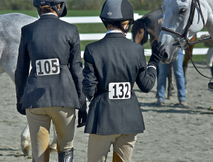 A pair of young New Jersey hunter-jumper riders prepare to walk the course.